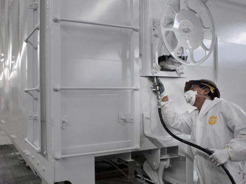 Worker painting railcar